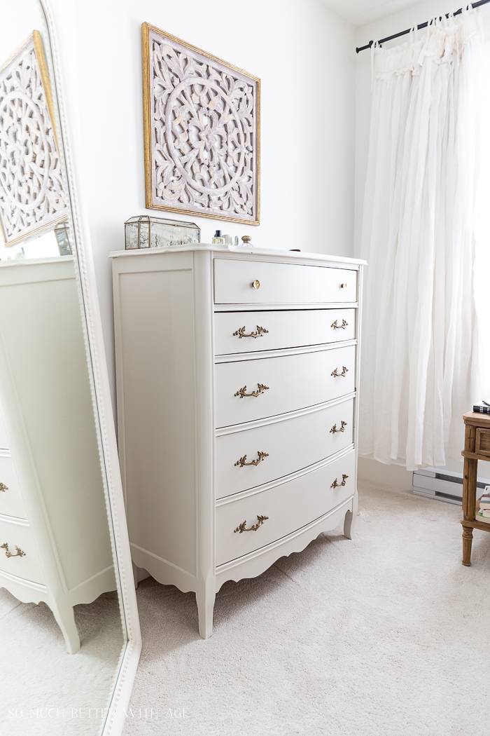 Cream colored painted dresser with wooden art above on wall in a bedroom.