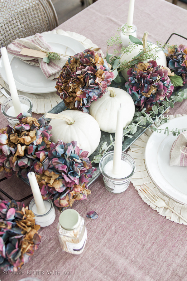 French Fall Home Tour with Purple and Green / Purple hydrangeas, purple French linen tablecloth, white pumpkins, seeded eucalyptus green, candles on table - So Much Better With Age