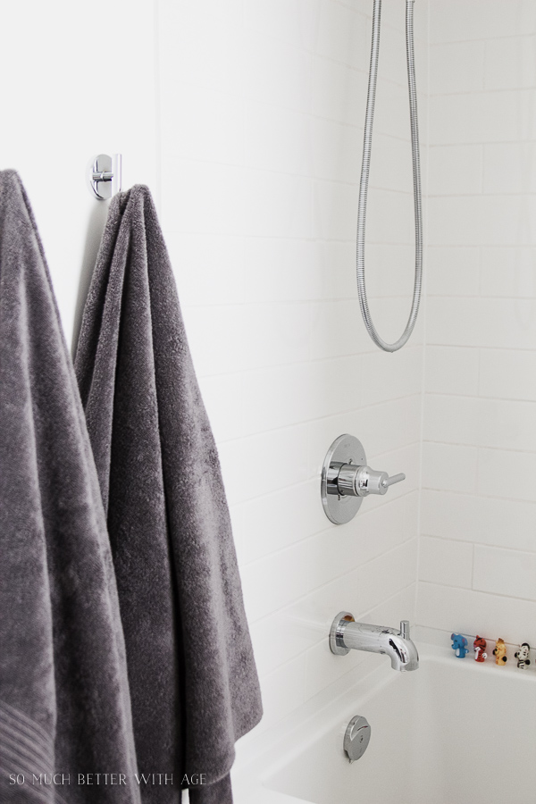 Simple clean and white kids bathroom reveal / White subway tile, clean simple white bathroom, grey towels - So Much Better With Age