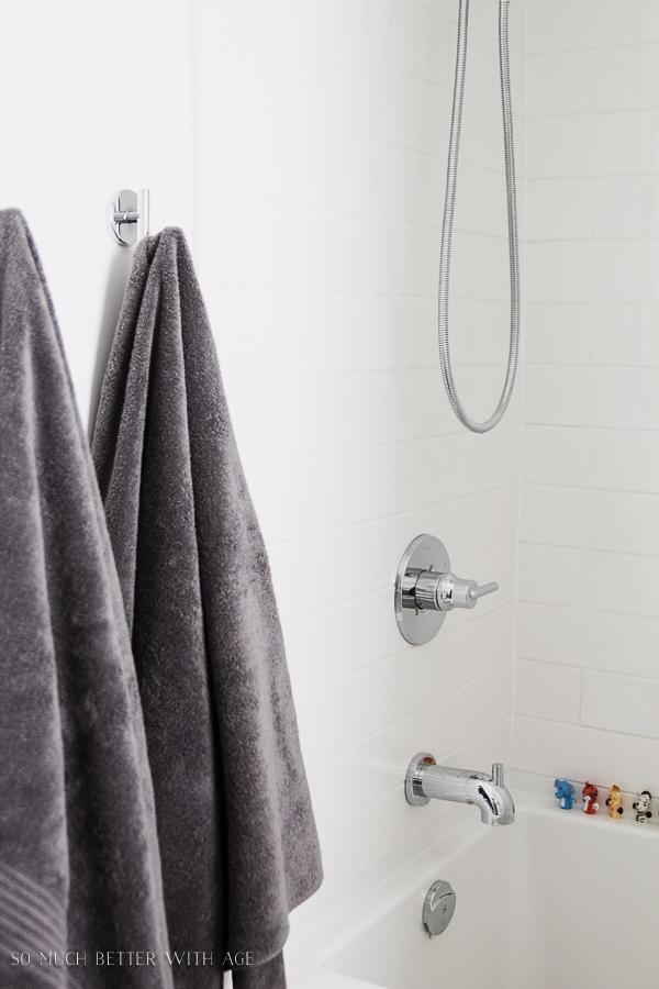 White subway tile, clean simple white bathroom, grey towels