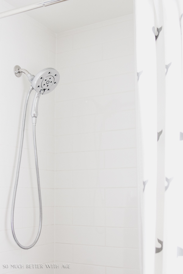Simple clean and white kids bathroom reveal / White subway tile bathroom with Delta Triassic showerhead - So Much Better With Age
