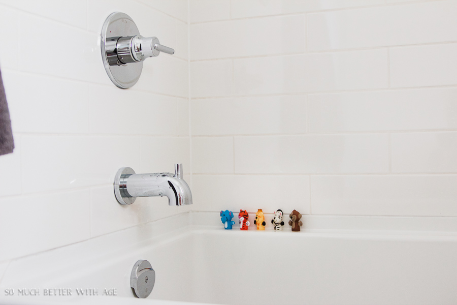 Simple clean and white kids bathroom reveal / White subway tile bathroom, Delta Trinsic faucet and children's bath toys - So Much Better With Age