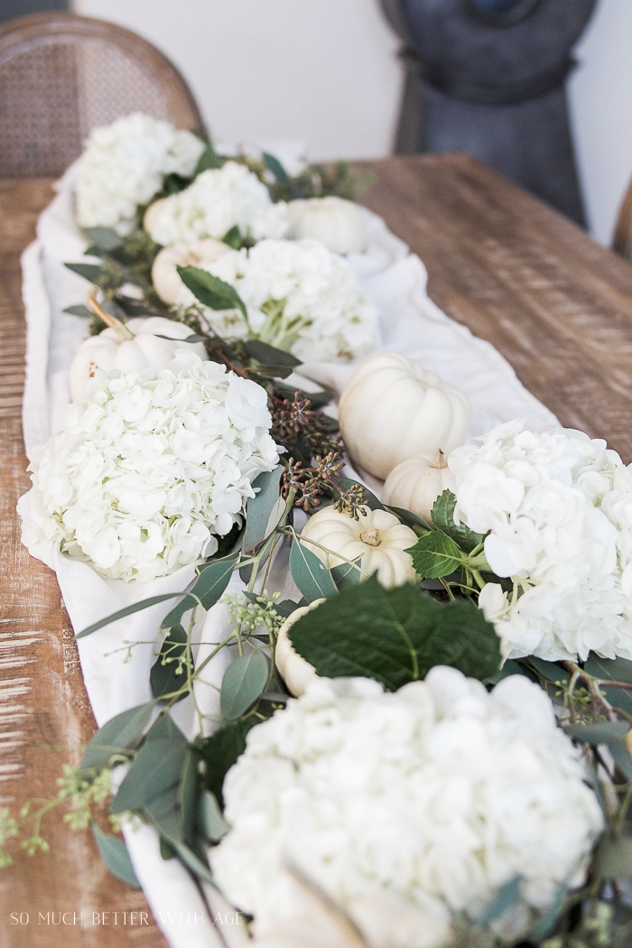 White pumpkins and hydrangeas plus seeded eucalyptus are on the table.