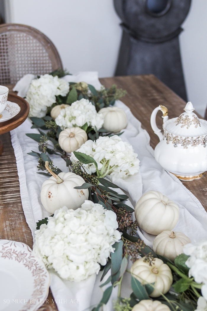There is a tea pot on the table beside the white runner filled with fall items.