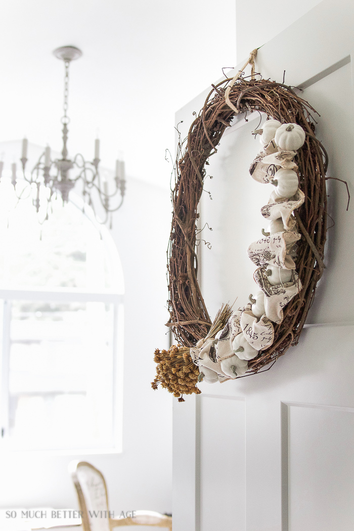 Wreath on door with chandelier in background.