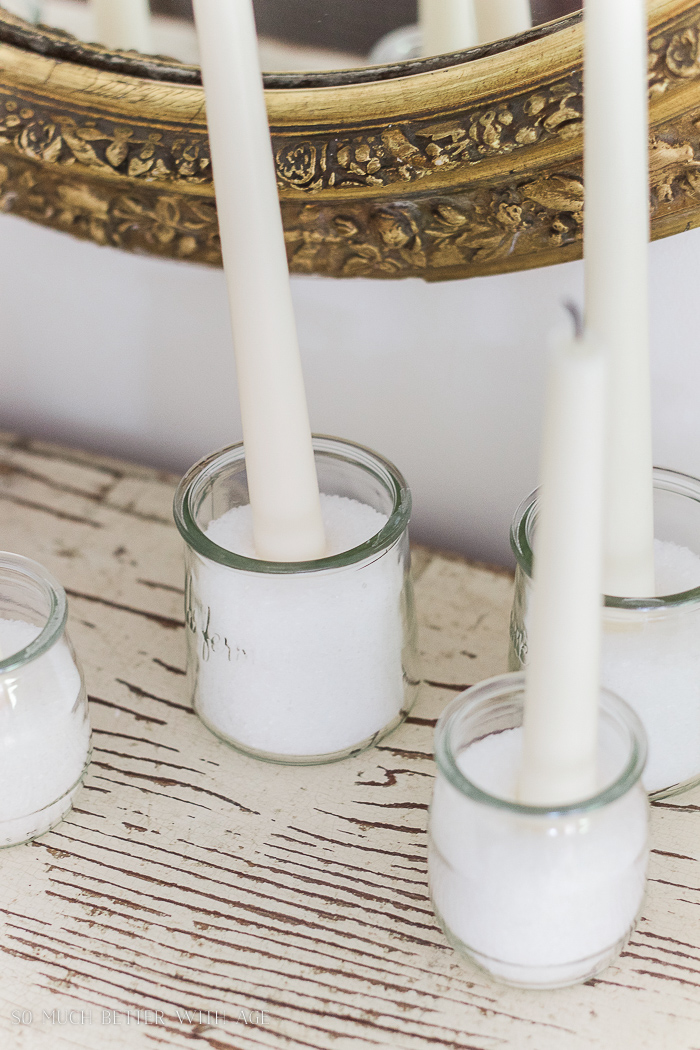 The jars with white candles on a wooden table.
