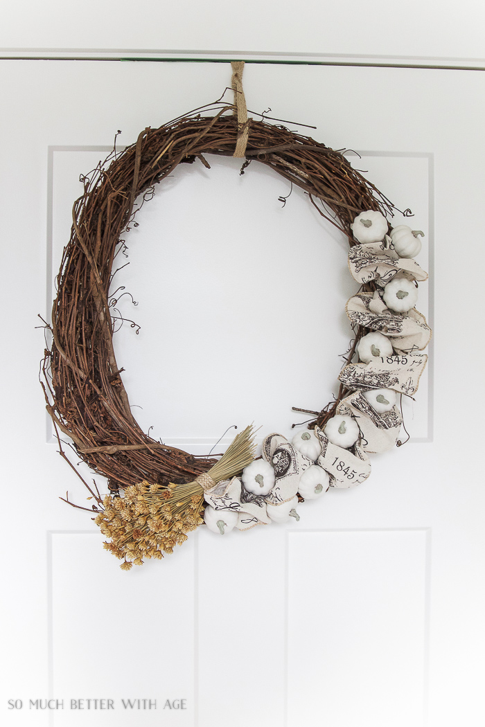 Grapevine wreath with white pumpkins and dried flowers hanging on door.