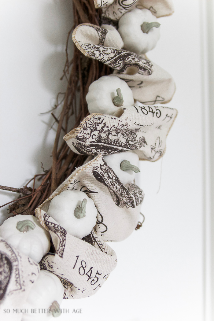 White small pumpkins on wreath with ribbon in between.