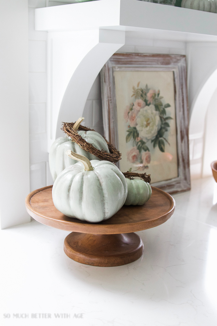 green heirloom pumpkins on wooden cake stand- Fall Kitchen Tour