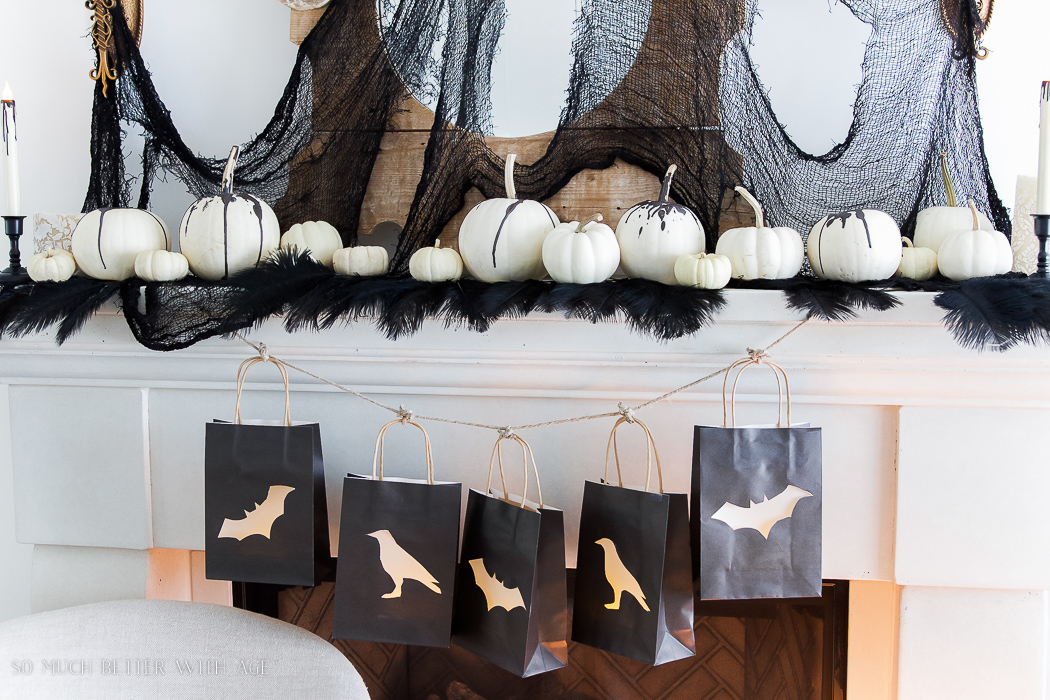 White pumpkins with black wax, black lantern bags with crows & bats- Classic black Halloween mantel decor