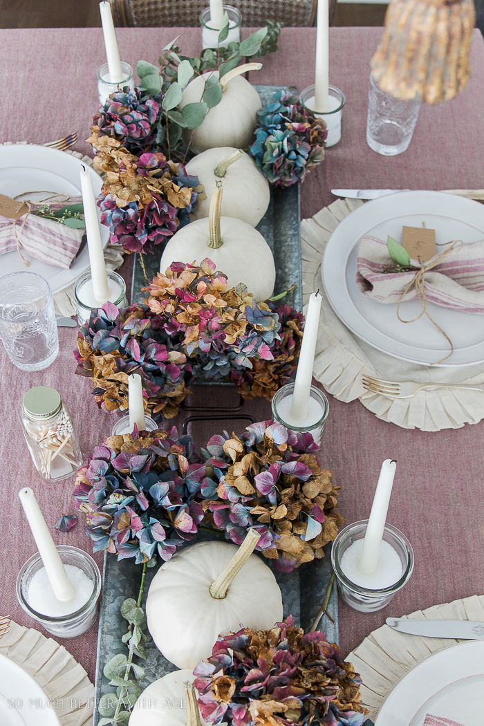 Hydrangeas, white pumpkins on the table with a pink tablecloth.