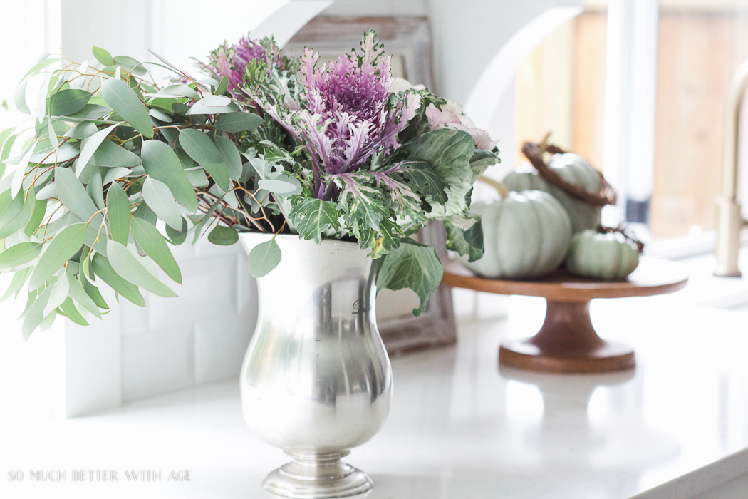 kale flowers with eucalyptus in silver pitcher- Fall Kitchen Tour