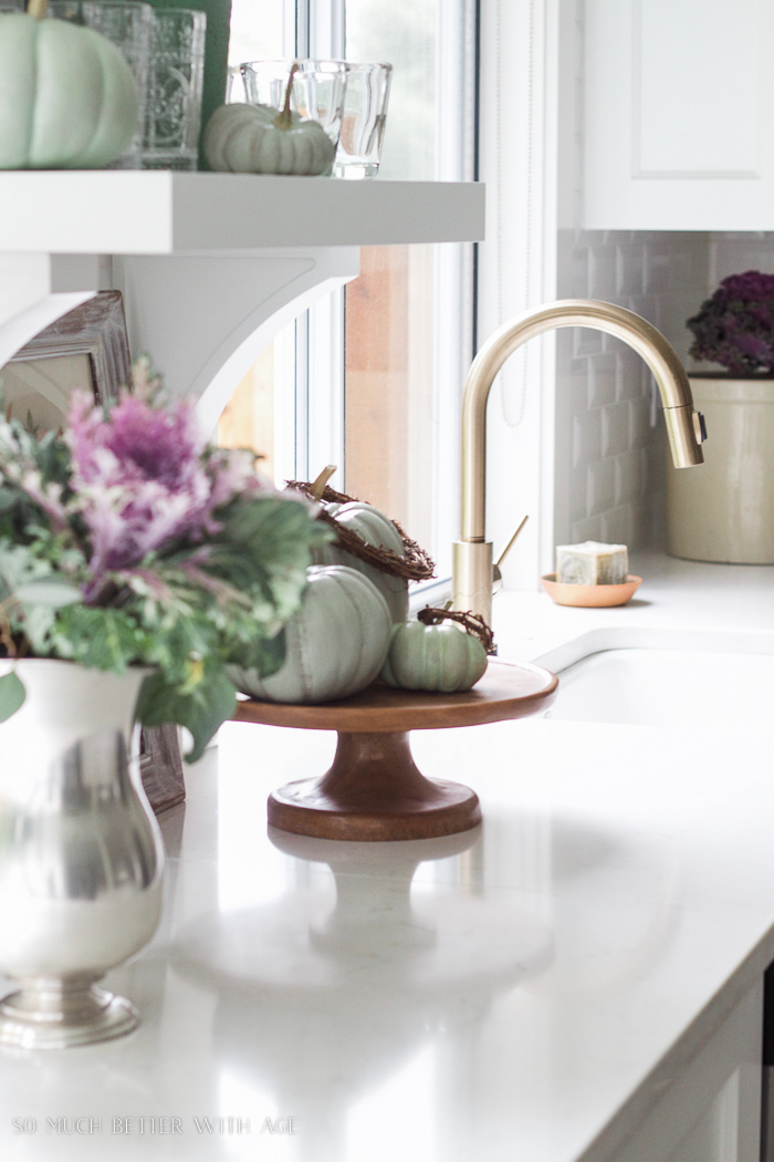 kale, eucalyptus floral arrangement, heirloom pumpkins, gold faucet- Fall Kitchen Tour