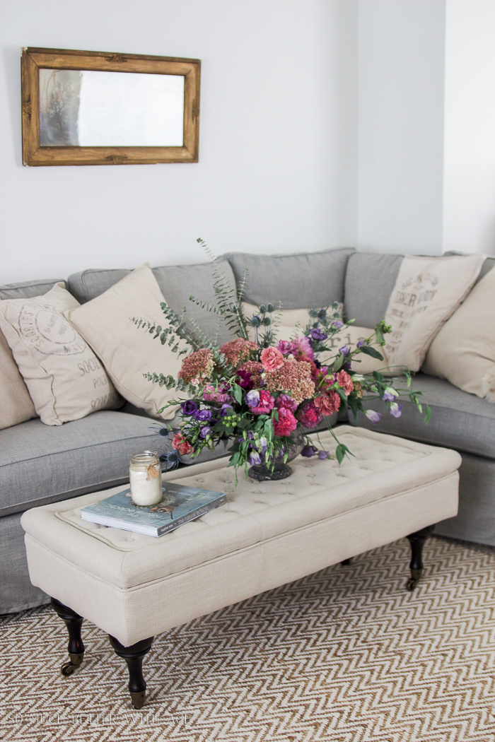 large floral arrangement, grey slipcovered couch- Fall Kitchen Tour