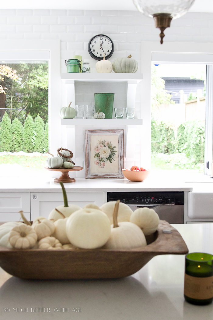 White kitchen, green glass, and a wooden bowl filled with white pumpkins.