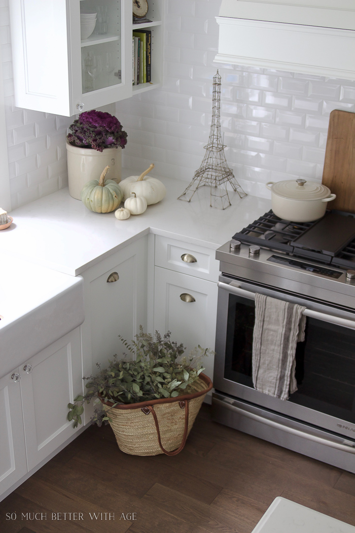 crock, kale plant, pumpkins, french market basket in white kitchen- Fall Kitchen Tour