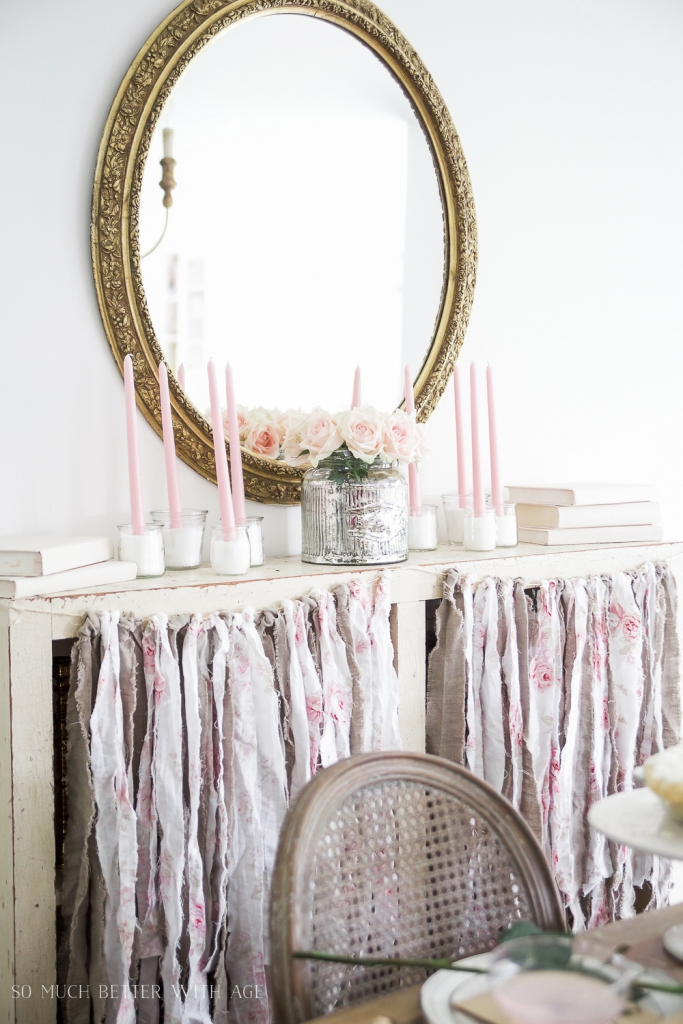 Gold mirror with roses, pink taper candles, pink fabric garland.