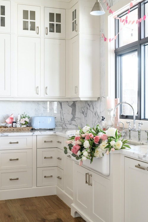 Pink and white roses on a white kitchen sink.