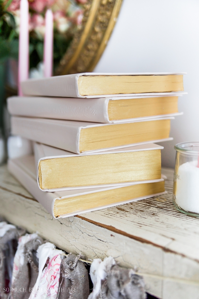 The stacked painted books with gold and pink.