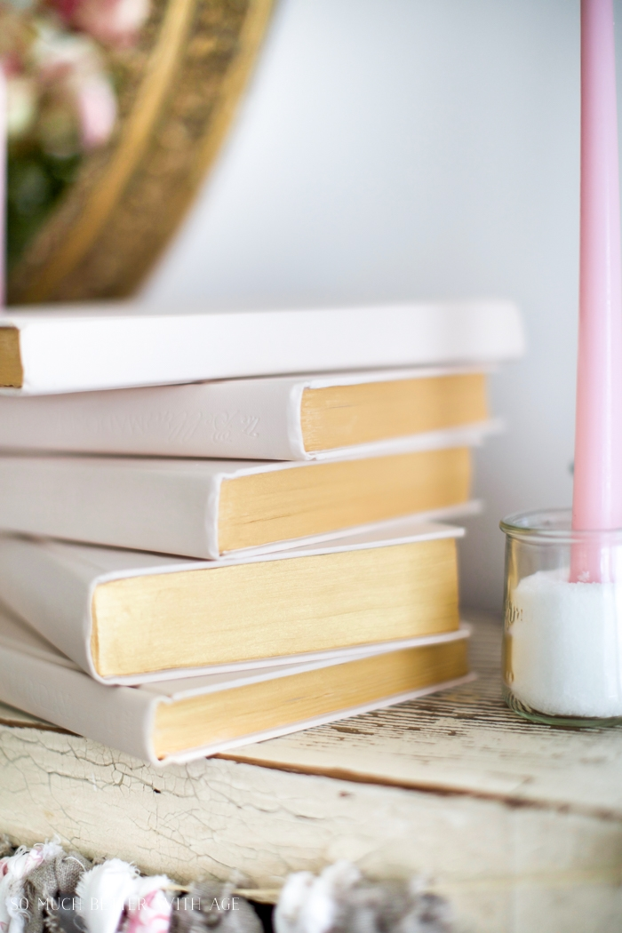 There is a pink candle beside the old books.