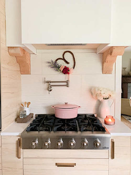 An old stove with a pink pot on top of it.