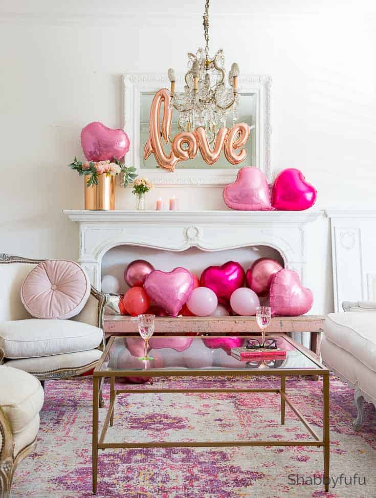 A living room with a fireplace filled with heart balloons.