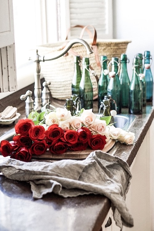 Red and white roses beside the sink in the kitchen.