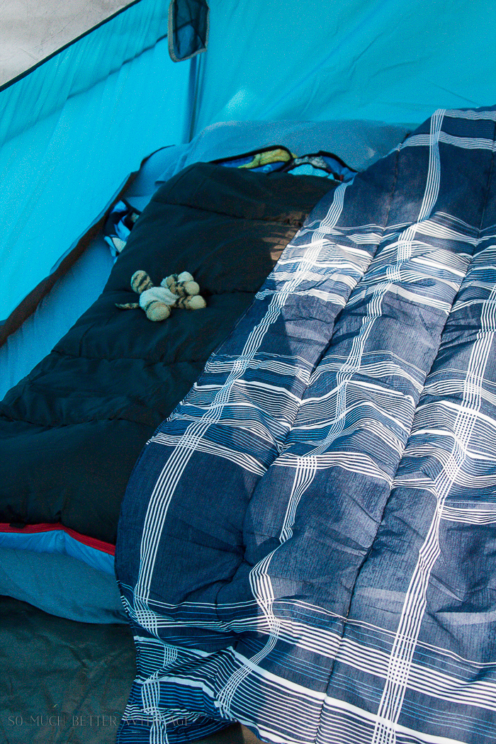 Stuffed toy animal on bed in tent.