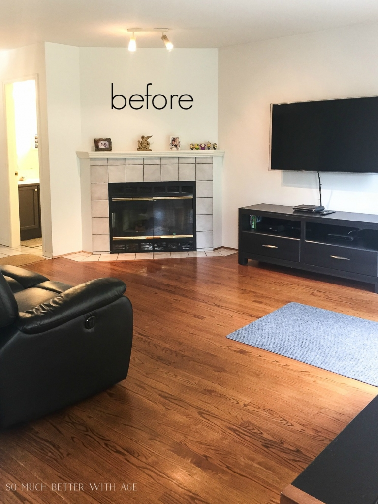 Before family room with corner fireplace and black leather couch.