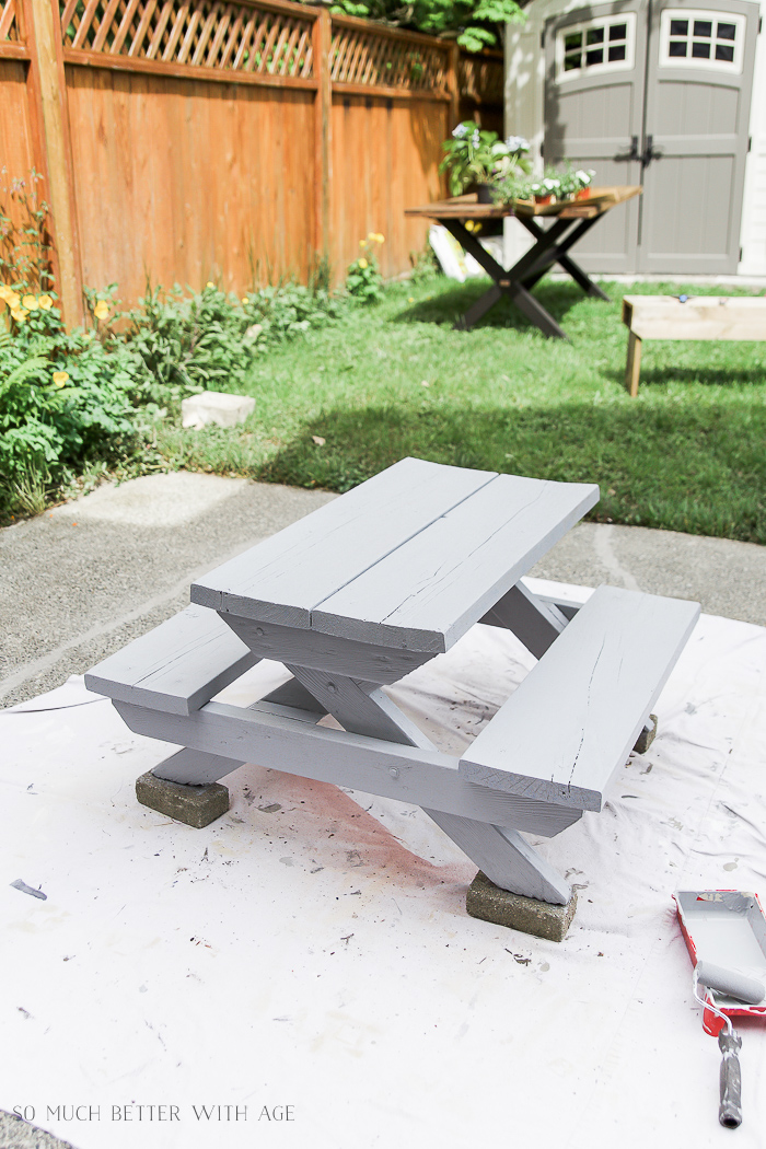 The first coat of paint on the small picnic table.