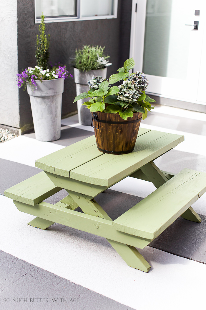 The table painted a light green on the patio.