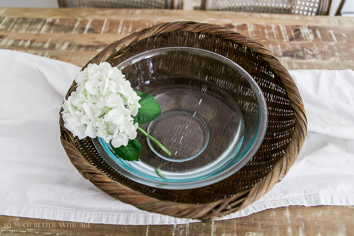 Glass bowl inside of basket with white flower.