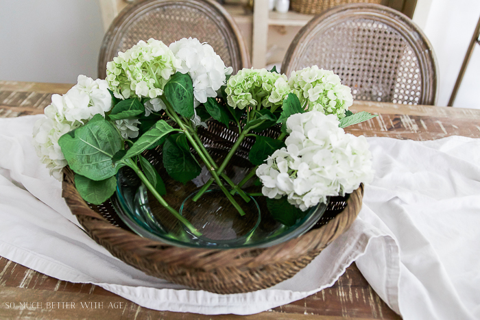 Lots of white flowers in glass bowl on table.