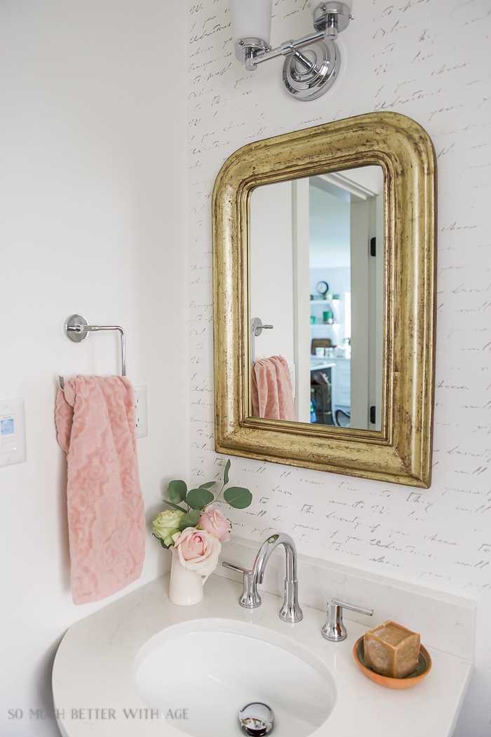 Gold mirror in powder room with pink accents.