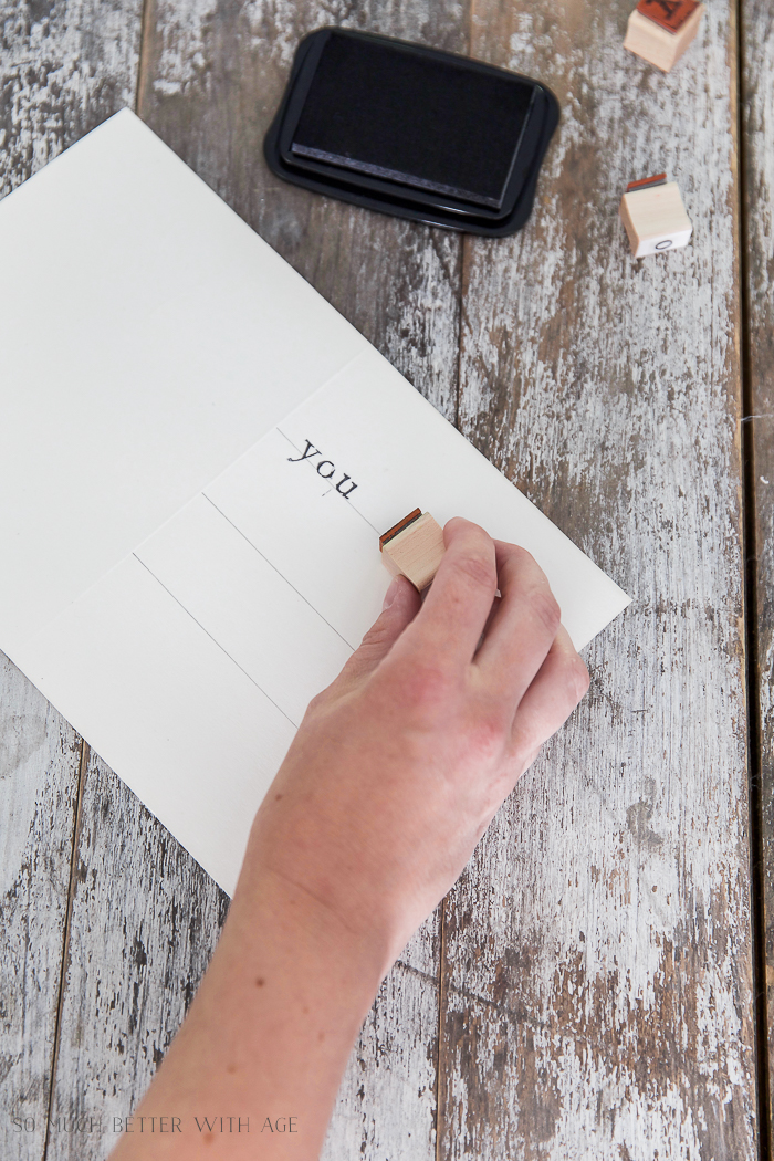 Stamping the word YOU onto the white piece of paper with pencil lines.