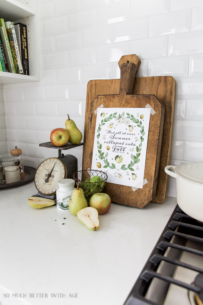 Apples and eucalyptus free fall printable on the cutting board in the kitchen.
