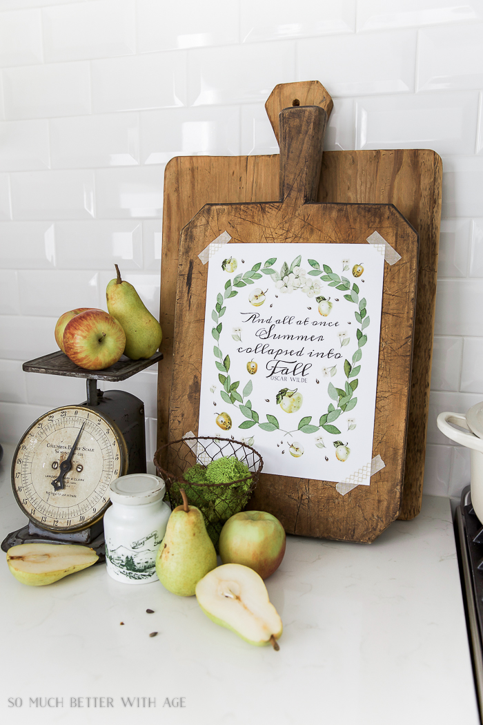 Apples and eucalyptus free fall printable taped to the bread board with apples and pears on the counter too.