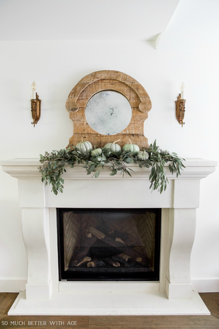 Rustic mirror, heirloom pumpkins on the fireplace mantel.