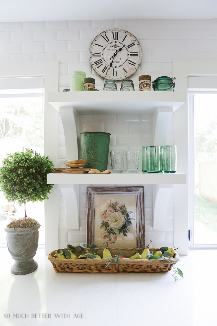 Open white shelves in kitchen with green glass and green bucket and floral picture on counter.
