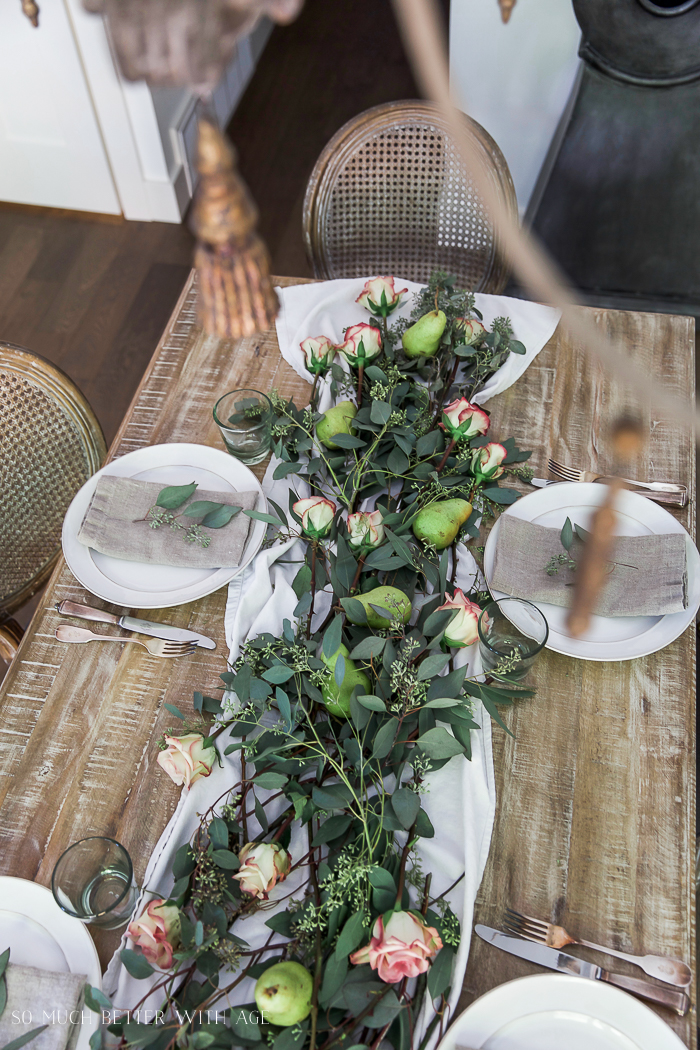 Wooden table with floral and eucalyptus table setting.