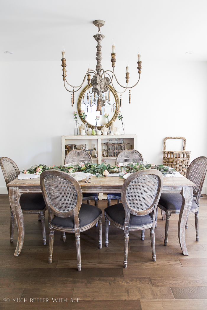 Dining room table with wooden chandelier above table.
