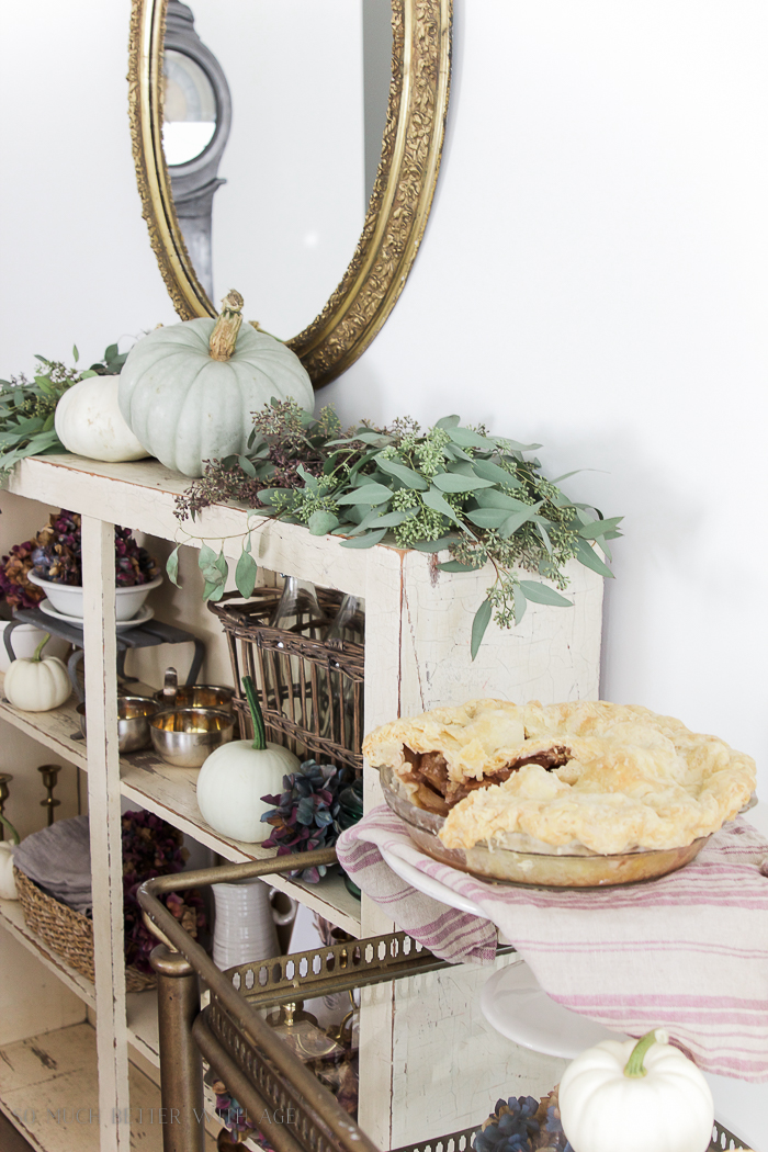 Eucalyptus on wooden shelf with a pumpkin pie on serving tray.