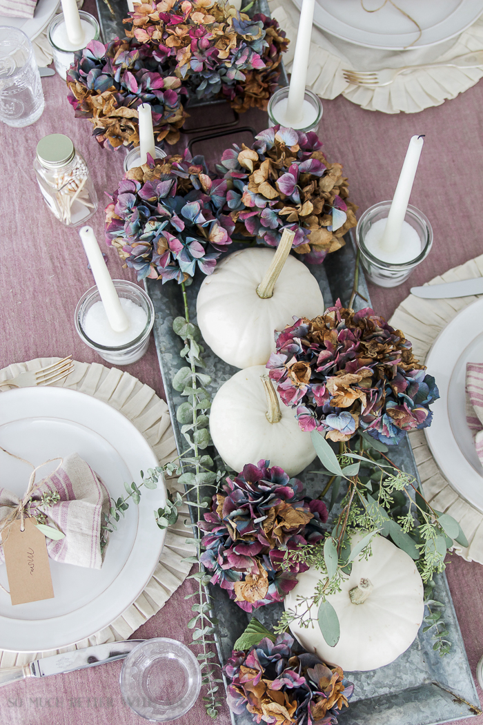 Dried blue and purple hydrangeas on the table with white candles and white plates.