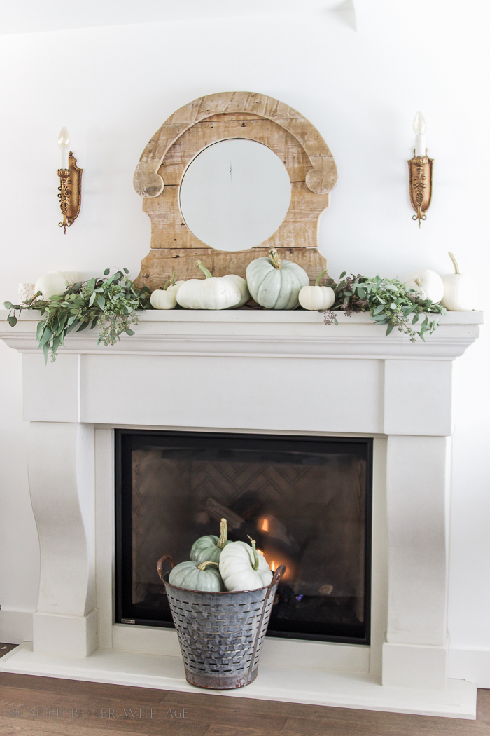 White neutral fireplace with mirror above it and pumpkins on mantel.