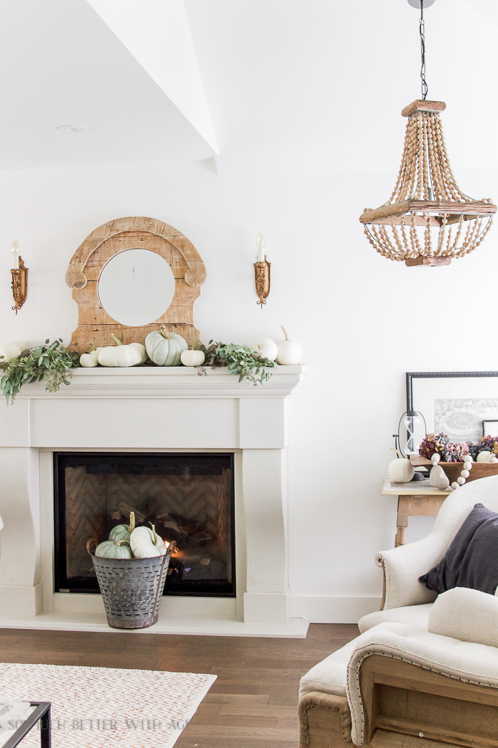 White fireplace mantel with an olive bucket in front of it filled with mini pumpkins.