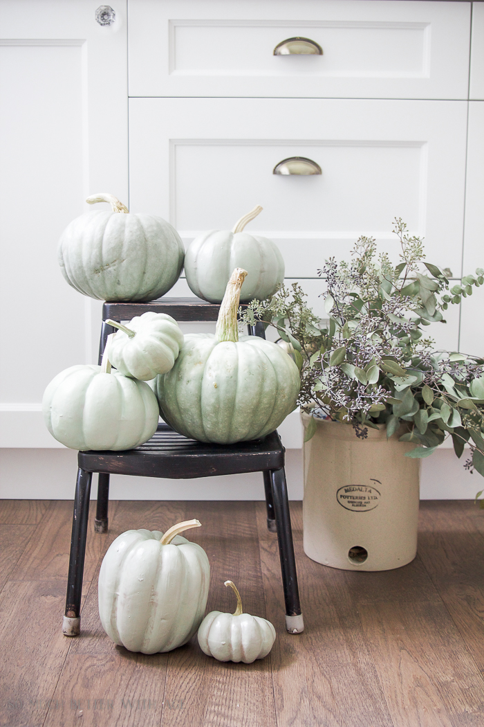 Heirloom pumpkins on a step ladder with a crock filled with eucalyptus beside it.