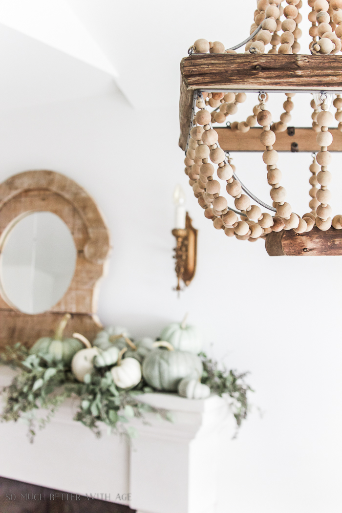 Wooden beaded chandelier near the mantel on the ceiling.