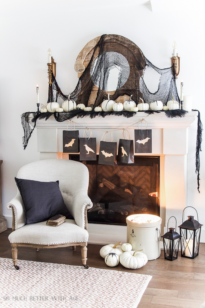 Black and white bats and crows hanging on the mantel with mini pumpkins on top of mantel.
