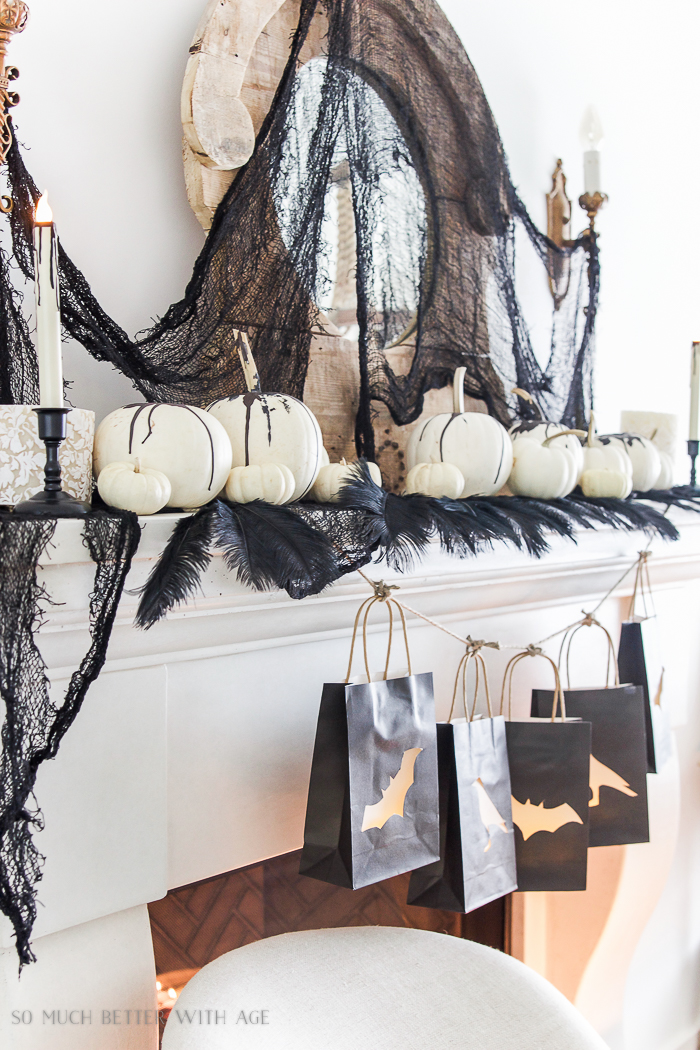White pumpkins on mantel with drips of black paint on them.