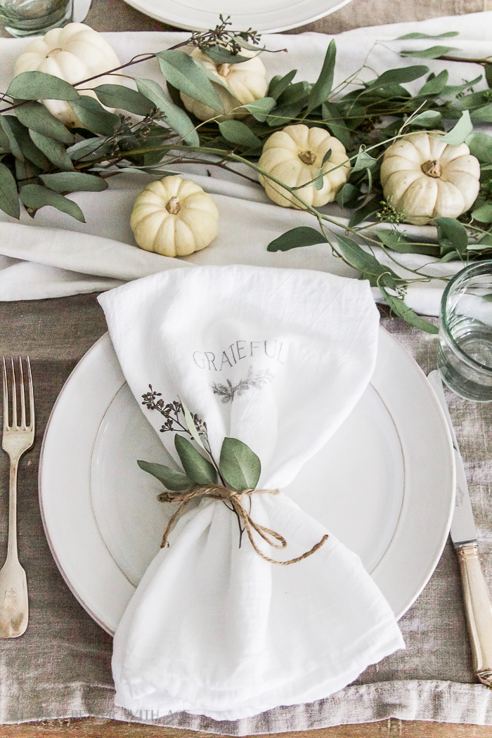 White napkin with grateful on it tied with eucalptus.